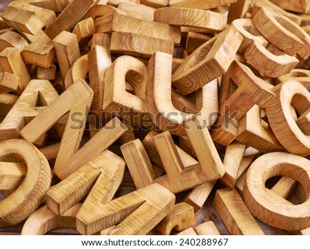 Surface covered with multiple wooden letters as a typography background composition