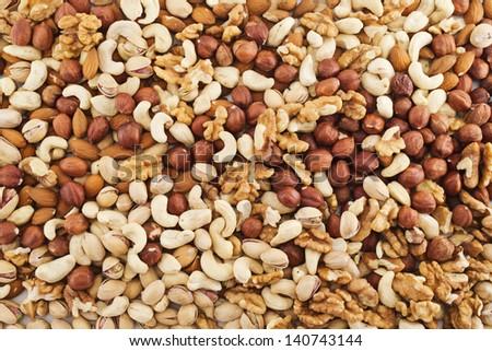 Surface covered with peanut, hazelnut, walnut, almond, pistachio nut mix - stock photo