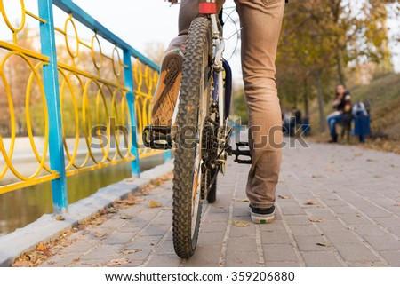 Surface Level View of YOung Man Riding Bicycle with Close Up on Rear Tire - Rider Taking a Break While Riding on Waterfront Path with Colorful Railing in Urban Park on Autumn Day - stock photo