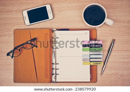 surface of a wooden table with notebook, smartphone, eye glasses, wooden clips with days and pen - stock photo