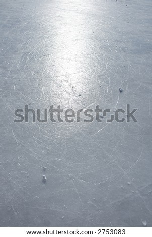 Surface of an outdoor ice rink replete with skate marks reflects the sun. - stock photo