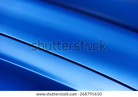 Surface of blue sport sedan car metal hood; part of vehicle bodywork  - stock photo