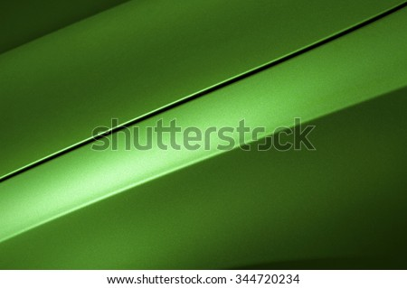 Surface of green sport sedan car, detail of metal hood and fender of vehicle bodywork - stock photo