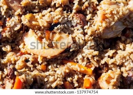 surface of pilau with quince and chickpea in outdoor cauldron - stock photo
