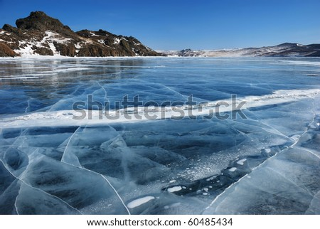 Surface of transparent fissured black ice of The Baikal Lake in winter - stock photo