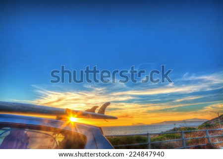 surfboard on a car rooftop at sunset - stock photo