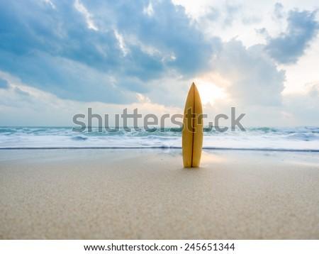 Surfboard on the beach at sunset - stock photo