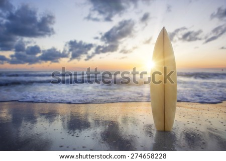 Surfboard on the beach at sunset - stock photo