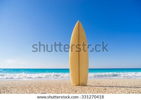 Surfboard on the beach  awaiting fun in the sun - stock photo