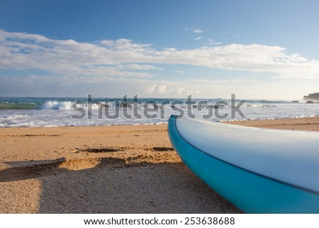 Surfboard resting on golden sand beach in early morning sunlight - stock photo