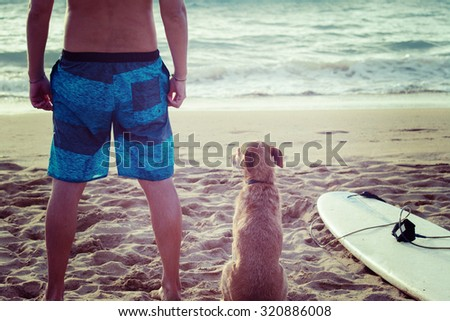 surfer and dog with a surfboard on the beach - stock photo
