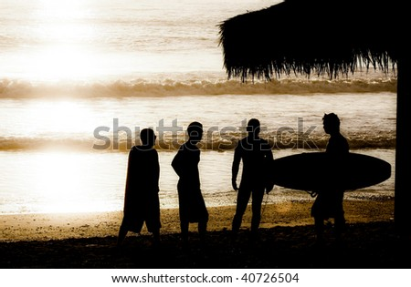 surfer and friends silhouette - stock photo