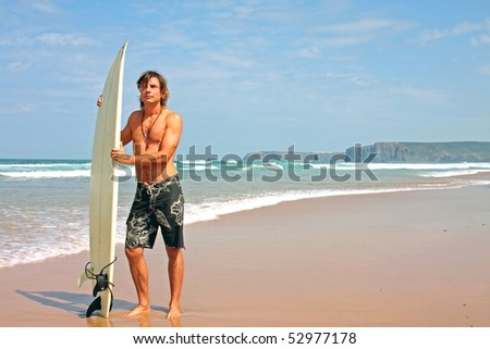 Surfer and his surfboard at the beach ready to surf on the atlantic ocean - stock photo
