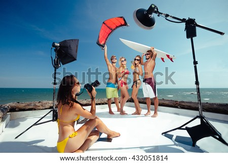 Surfer and kiter boys with beautiful girls group have photoshooting on beach  - stock photo