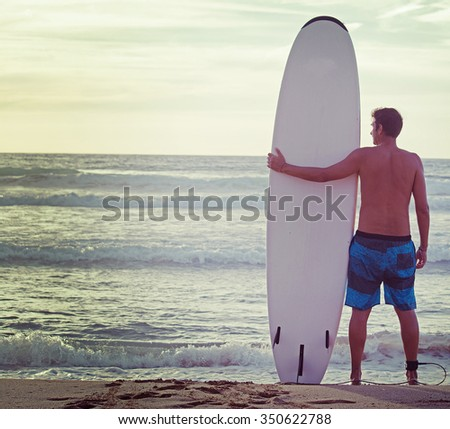 surfer and surfboard on the beach in vintage tone - stock photo