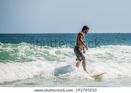 Surfer at Ilha Grande, Lopes Mendes beach. Funny. Brazil Rio do Janeiro. South America - stock photo