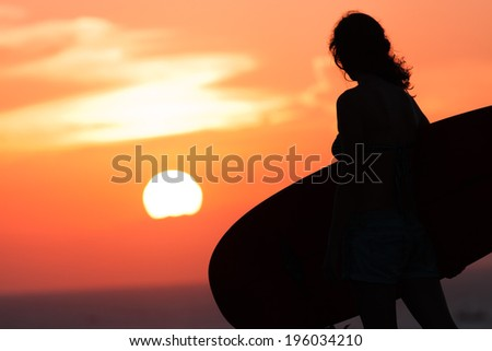 surfer at sunset with malibu surf board - stock photo