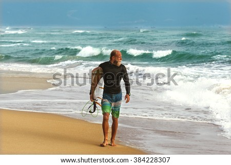 Surfer at the sea is standing with a surf board bright color.