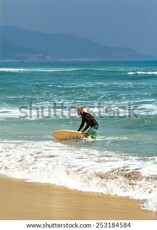 Surfer at the sea is standing with a surf board yellow color. - stock photo