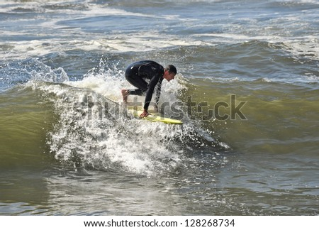 Surfer at the start of catching a wave in Oceanside, California. - stock photo