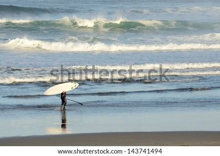 Surfer braving the cold water in the sunrise morning light at Pacific City Oregon with mild Pacific ocean surf - stock photo