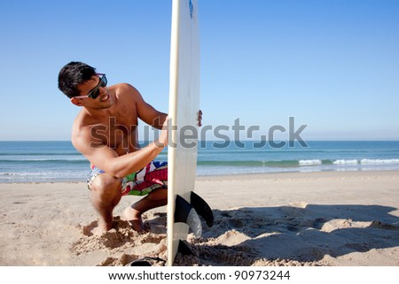Surfer checking his surf board on the sand. - stock photo