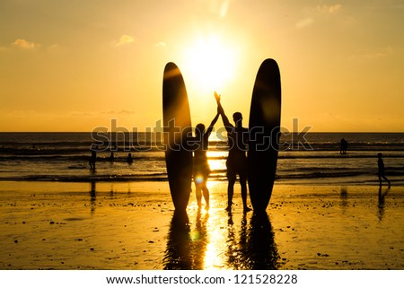 Surfer couple in silhouette holding long surf boards at sunset on tropical beach - stock photo