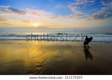 surfer entering water at the sunset