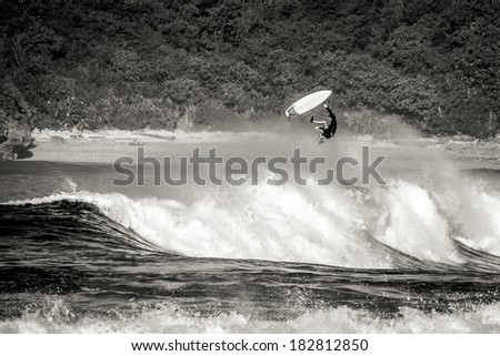 surfer getting big air and wiping out in rough indian surf - stock photo