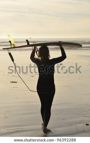 surfer girl carriing her board at sunset - stock photo