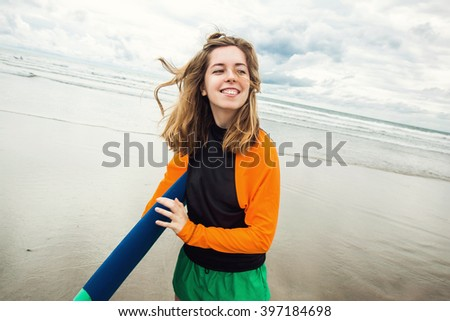 Surfer girl holding surf board and having fun on a beach of Kuta, Bali - stock photo
