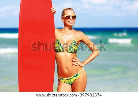 Surfer girl on the beach - stock photo