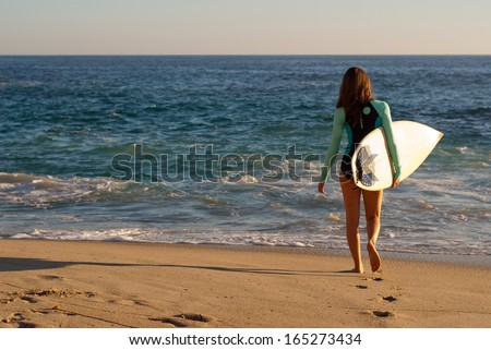 Surfer girl on the beach - Female surfer walking on the beach surfboard in hand with the ocean in the background. - stock photo