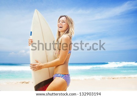 Surfer girl on the beach of bali - stock photo