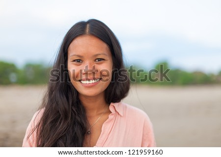 surfer girl posing on the beach and smiling - stock photo