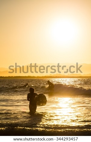 surfer girl walking in the water while sunset