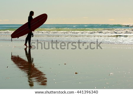Surfer girl with surfboard on the beach - stock photo