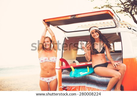 Surfer Girls Beach Lifestyle; Beautiful Surfer Girls Relaxing in the Back of Classic Vintage Surf Van on the Beach at Sunset - stock photo