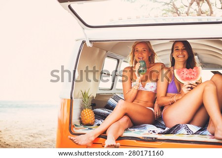Surfer Girls Beach Lifestyle, Friends Hanging out Eating Watermelon in the Back of Classic Vintage Surf Van on the Beach at Sunset  - stock photo
