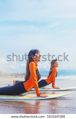Surfer girls in Bali practicing the correct position to stand on the board - stock photo