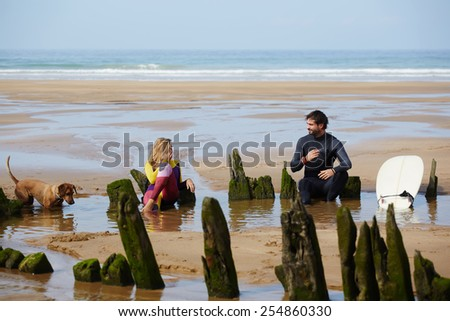 Surfer guys relaxing on the beach after good surf session, summer holidays on surf camp, international group of fancy surfers resting on the beach with beautiful shore with waves on background - stock photo