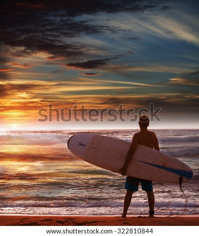 surfer holding a surfboard on the beach - stock photo