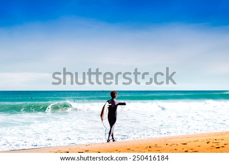 Surfer is going down the beach on a sunny day