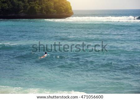 Surfer is going to serf in the ocean in a sunny day