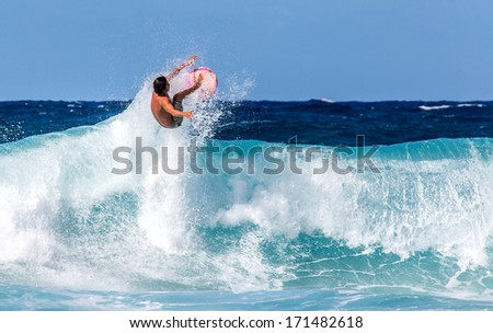 Surfer jumping above a wave on the North Shore of Oahu, Hawaii - stock photo