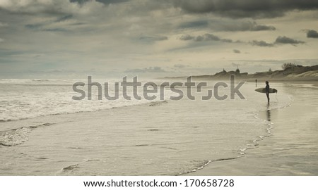 Surfer looking out at the sea - stock photo