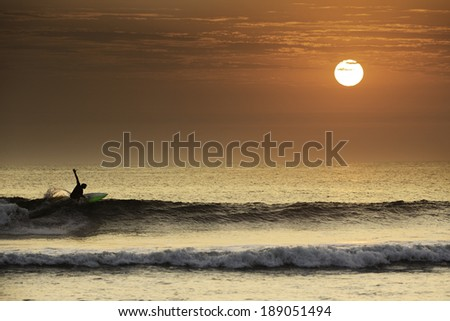 Surfer making a perfect turn in a beautiful sunset in northern Peru, South America. - stock photo