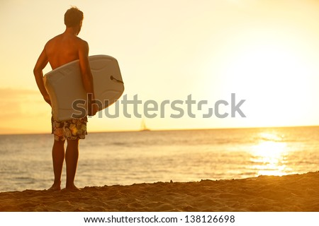 Surfer man on beach at sunset holding bodyboard. Fit male body surfer guy enjoying sunset and bodyboarding on summer holidays vacation on tropical beach. Fitness model, Kaanapali beach, Maui, Hawaii. - stock photo