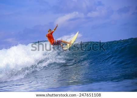 Surfer on Amazing Blue Wave, Bali island.