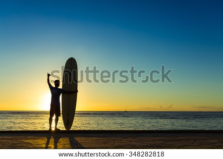 Surfer on Beach at Sunset - stock photo